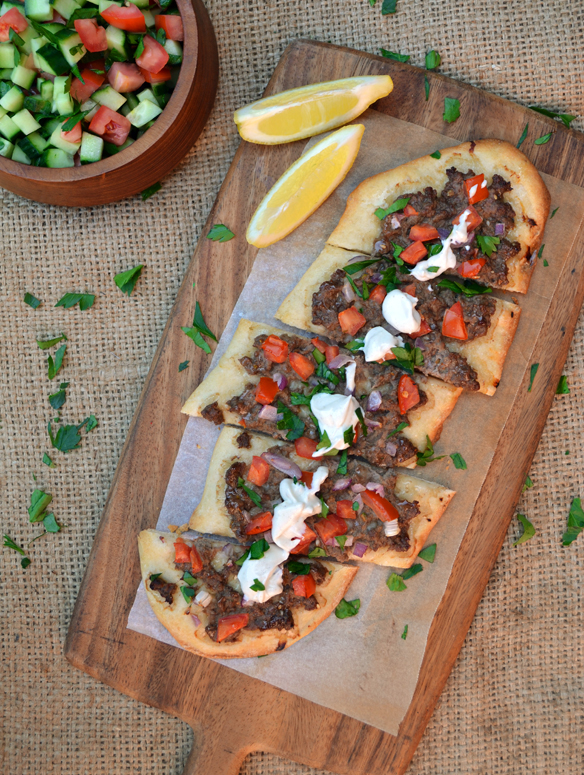 Spiced lamb pizza with tahini sauce. One Equals Two.